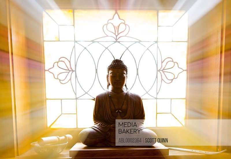 Seated Buddha Statue in front of Stained Glass Window