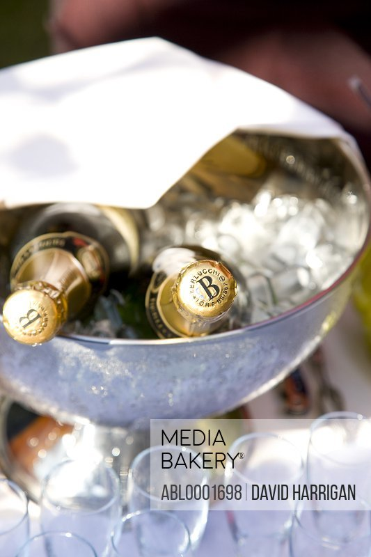 Close up of champagne bottles in an ice bucket and empty glasses