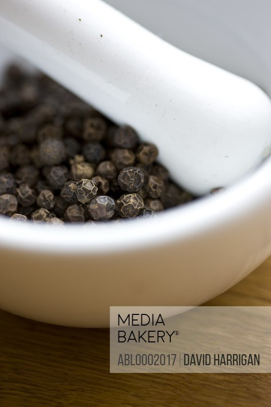 Mortar and Pestle Filled with Black Peppercorns