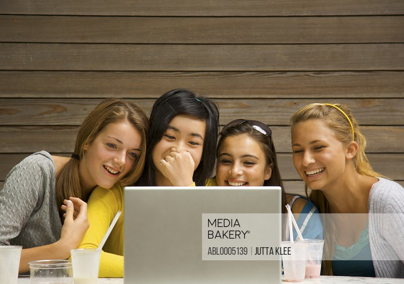Teenage girls sitting in front of laptop computer laughing