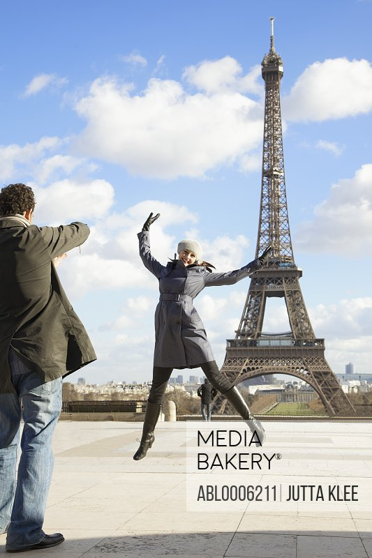 Back view of a man taking a photo of a woman in front of the Eiffel Tower