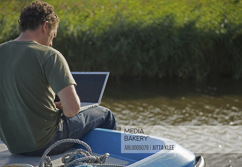 Back view of a man sitting on a boat using a laptop computer