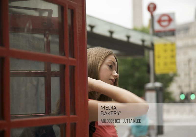 Teenaged girl exiting a London phone booth