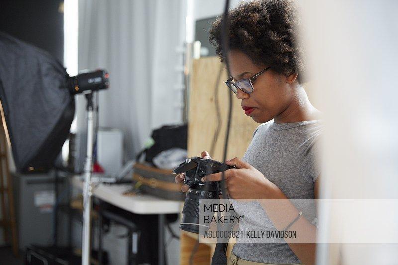 Female Photographer Holding Camera in her Studio