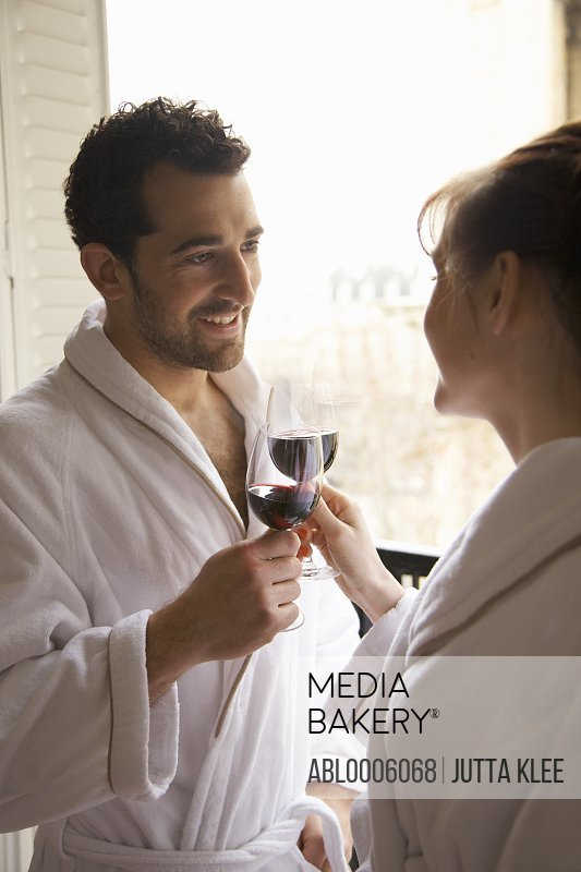 Couple toasting each other with red wine