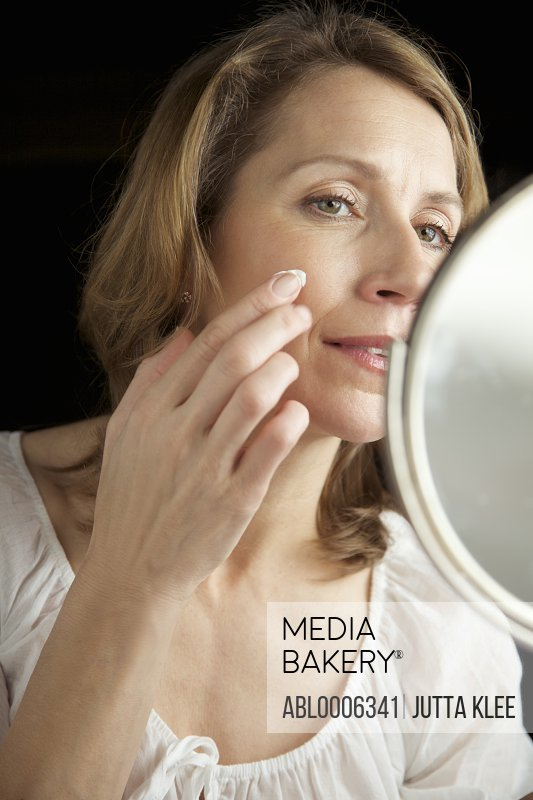 Close up of a woman looking into mirror applying cosmetic cream