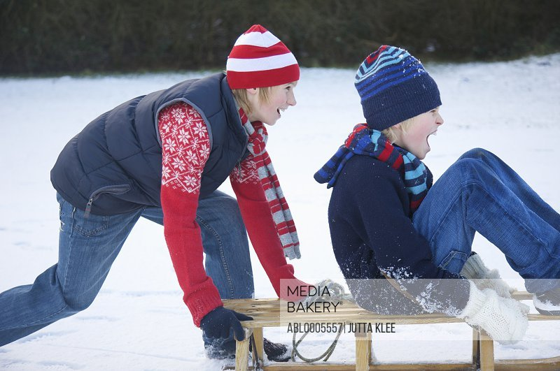 Profile of a  boy pushing a friend sitting on a sled