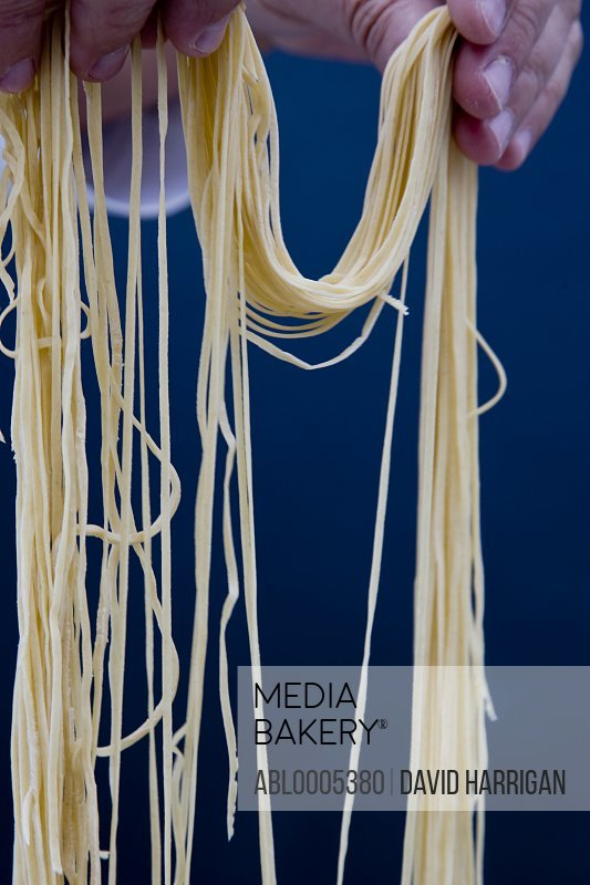 Close up of a hands holding angel hair pasta