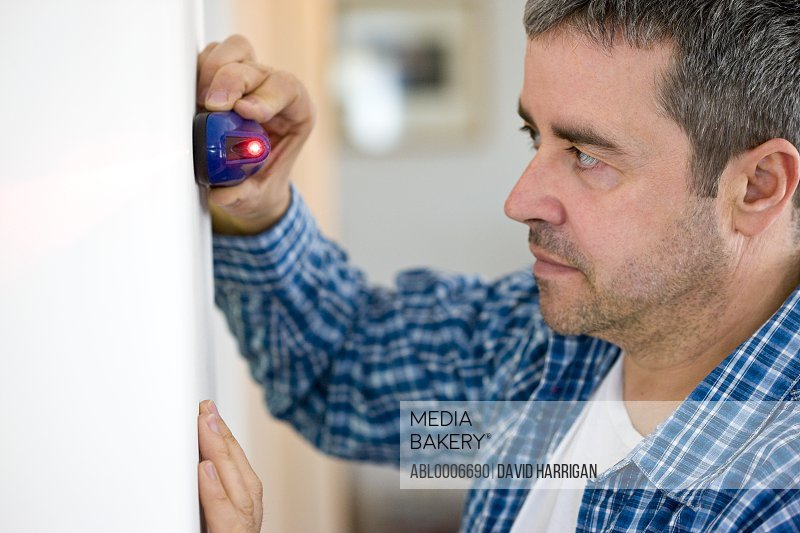 Profile of Man Holding Laser Level against White Wall