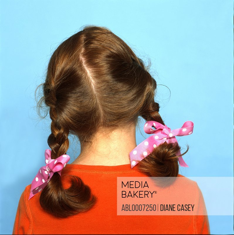 Back View of Girl's Head with Braids and Pink Ribbons