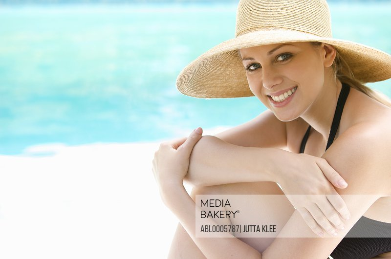 Smiling young woman wearing a straw hat sitting by a swimming pool