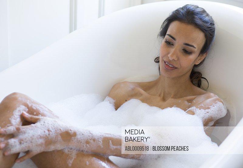 Woman in Bubble Bath Washing her Leg