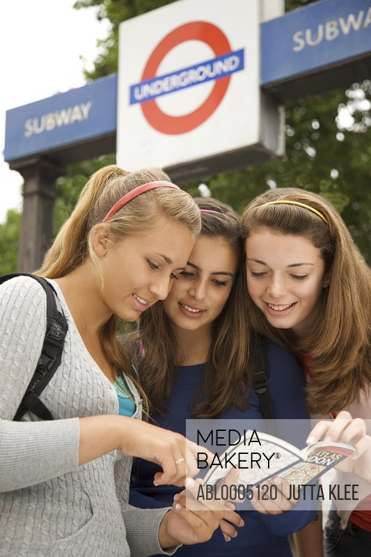 Three teenaged girls exiting the London underground inspecting a map