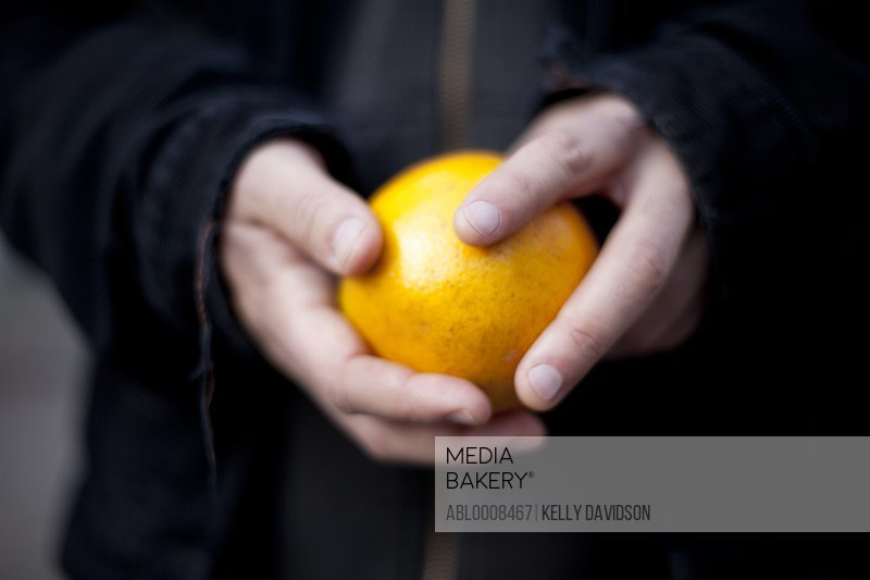 Man Holding Orange, Close-up View
