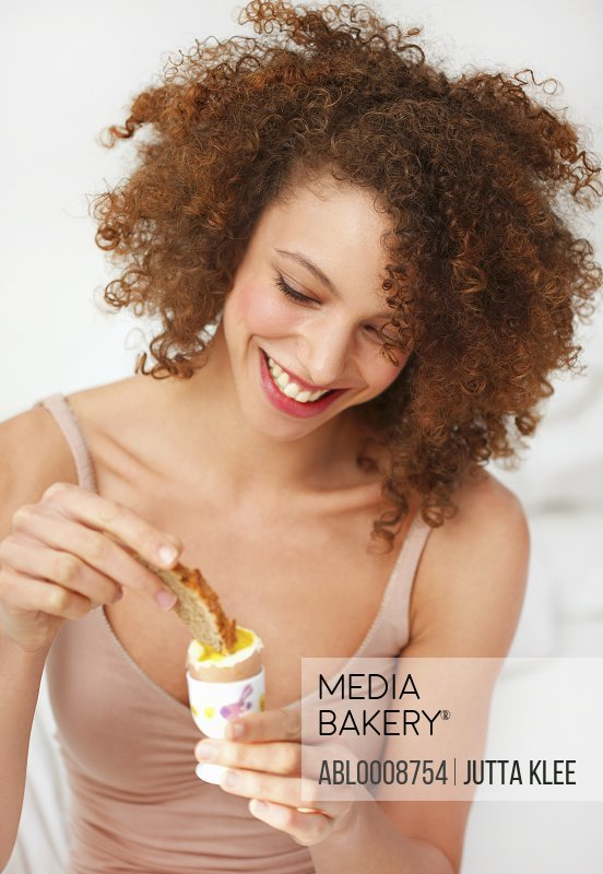 Smiling Woman Dipping Toast in Soft Boiled Egg