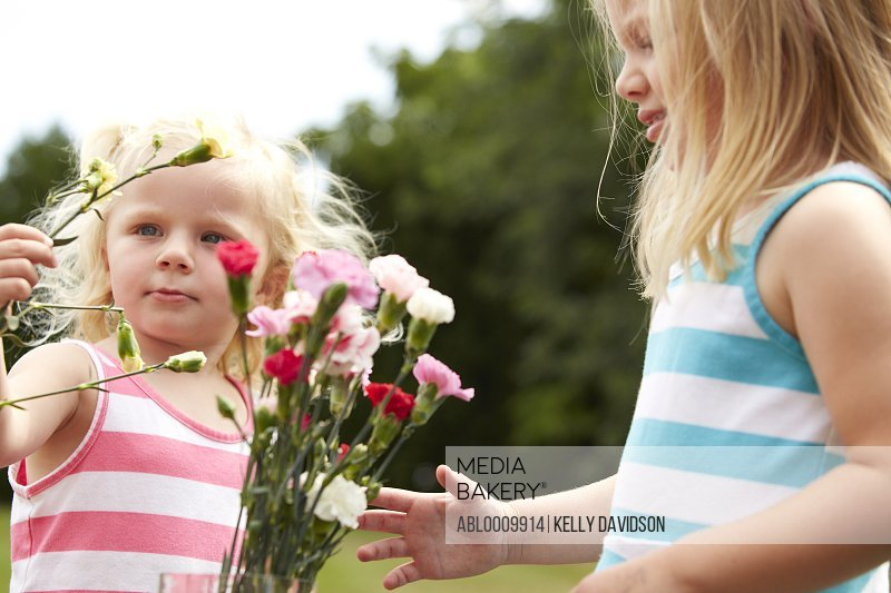 Two Young Girls Arranging Flowers Outdoors