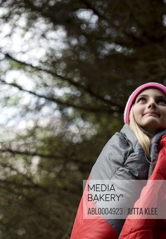 Standing teenaged girl wrapped in a sleeping bag looking up and smiling