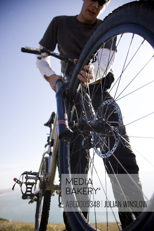 Man checking the wheel of a bicycle