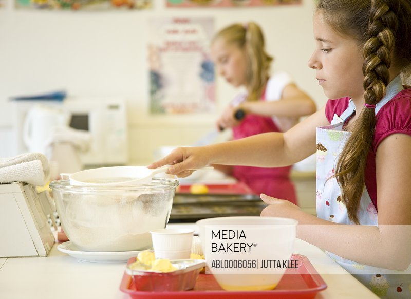 Young girls in cookery class baking