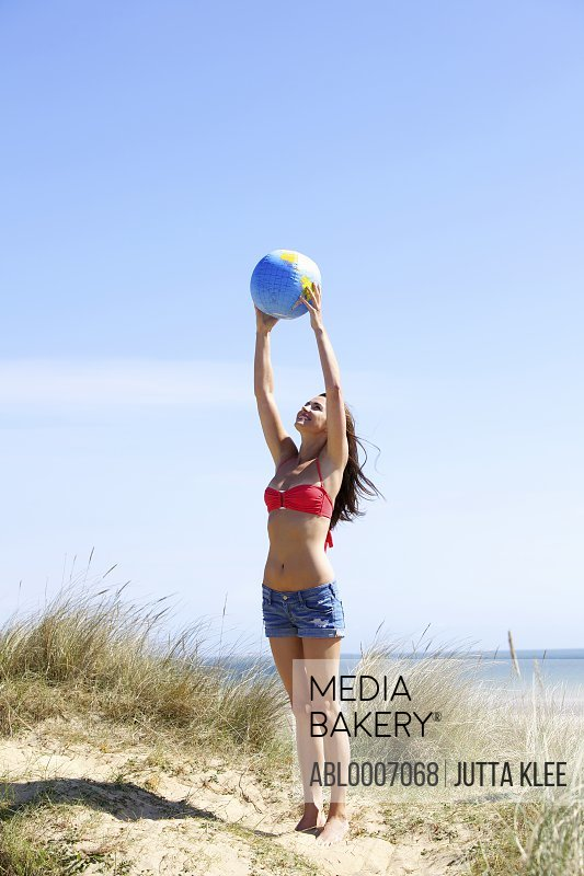 Woman Holding Ball above Head at Beach