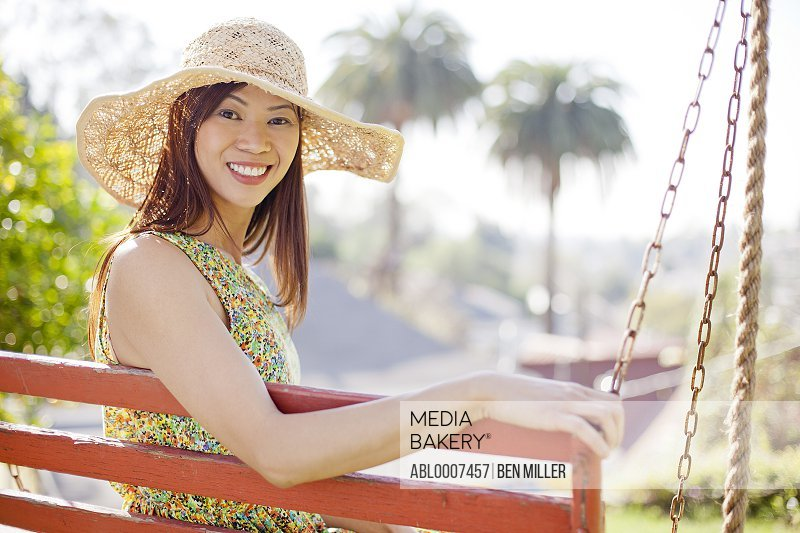 Smiling Woman Wearing Straw Hat Sitting on Porch Swing
