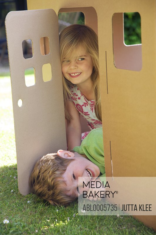 Boy and girl smiling in the doorway of a cardboard playhouse
