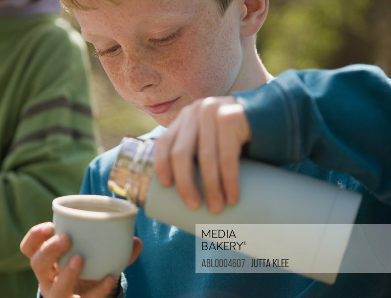 Close up of boy pouring water from insulated flask