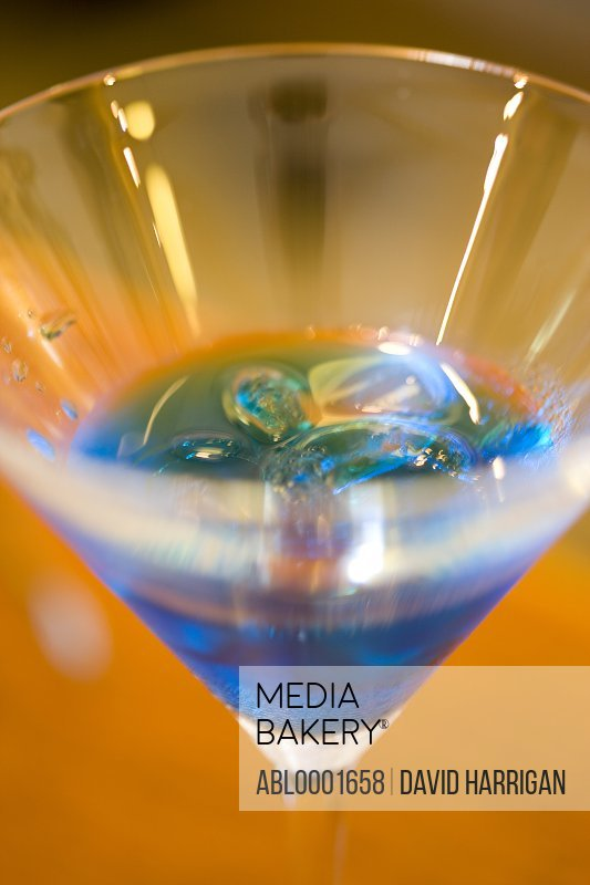 Close up of a martini glass with blue liquor and ice