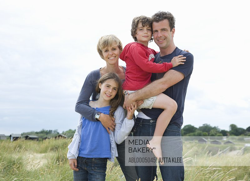 Portrait of family standing on a beach smiling