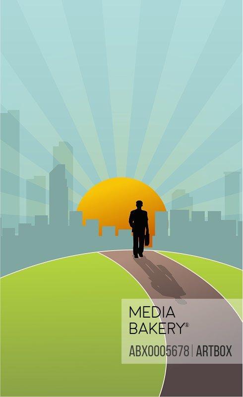 Businessman walking towards a city at sunset