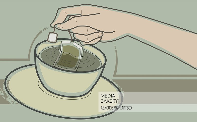 Human hand dipping teabag in a tea cup