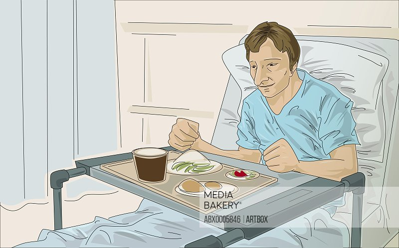 Male patient in a hospital bed with food in front of him
