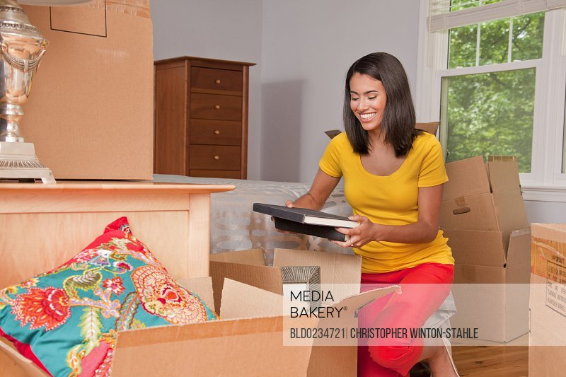 Hispanic woman kneeling on floor packing books in moving boxes
