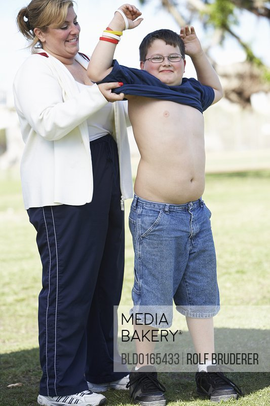 Mother helping son put on t-shirt