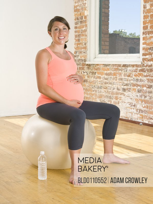 Pregnant Caucasian woman sitting on exercise ball
