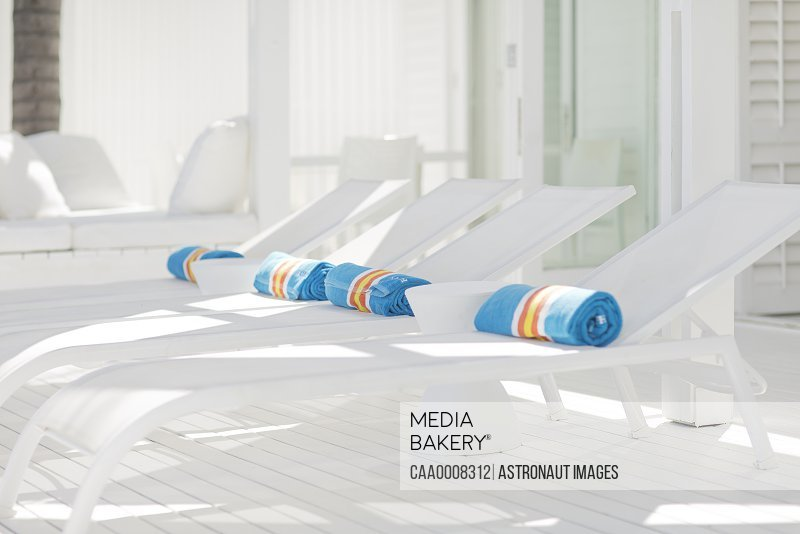 Striped towels rolled up on white lounge chairs/n