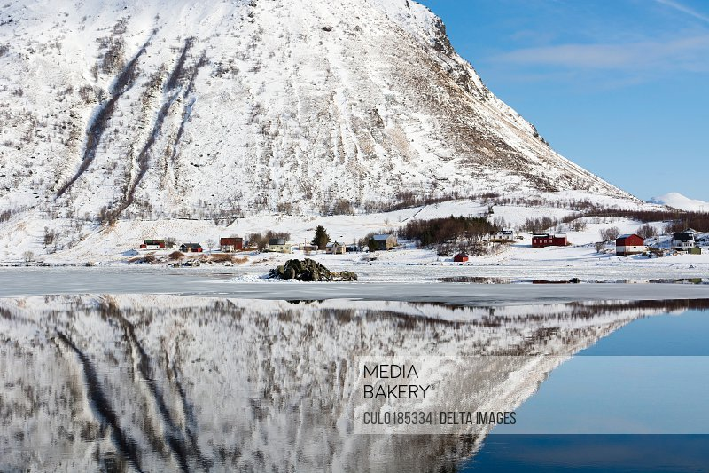 Snow covered mountain reflected in water Knutstad Lofoten Islands Norway