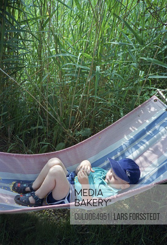 Toddler boy laying in hammock