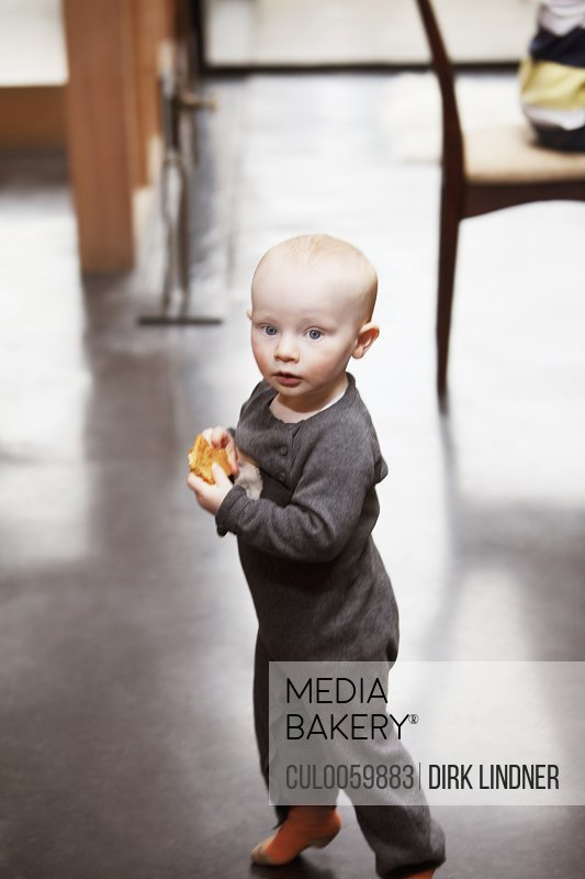 Toddler boy carrying a cookie