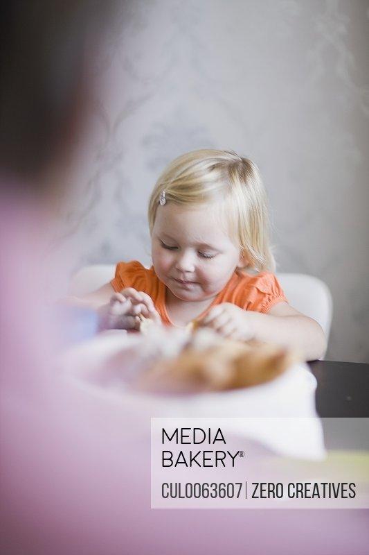 Toddler girl eating at dinner table
