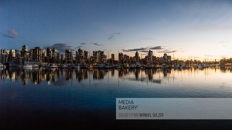 Harbour waterfront and city skyline at dusk Vancouver Canada