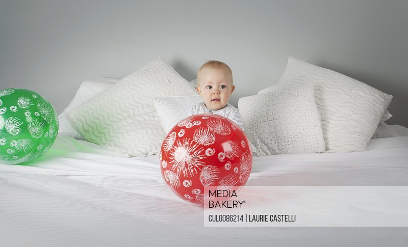 Baby boy playing with balloon on bed