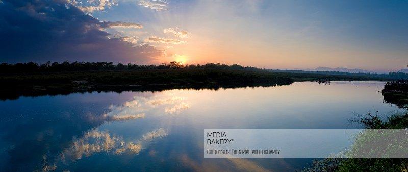 Sunrise reflected in still rural lake