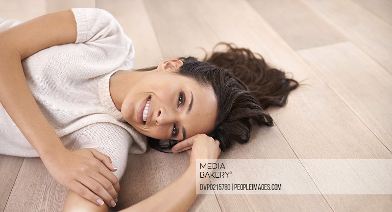A young woman smiling at the camera as she lies on the floor