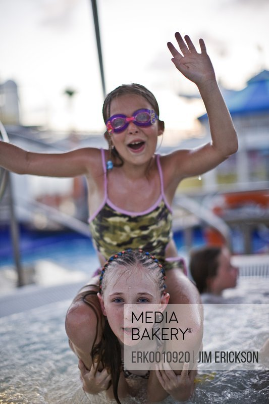 Portrait of two girls giving each other a shoulder ride while having fun in a swimming pool.