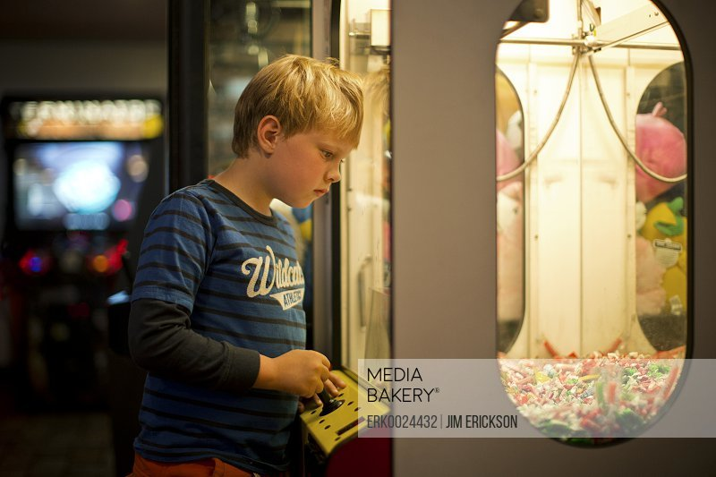 Young boy looking at an arcade game.