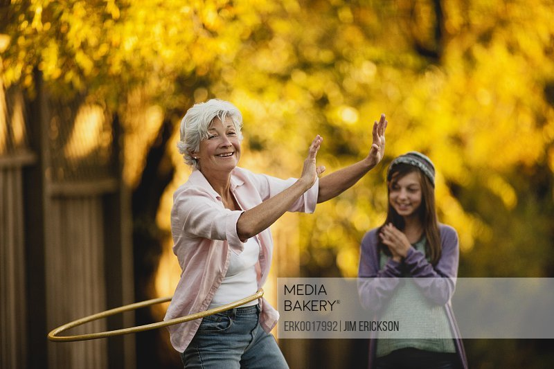 Young girl watches her grandmother hula hooping.