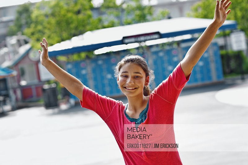Portrait of a smiling teenage girl waving her arms in the air.