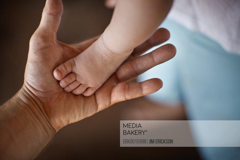 Baby's foot in hand.