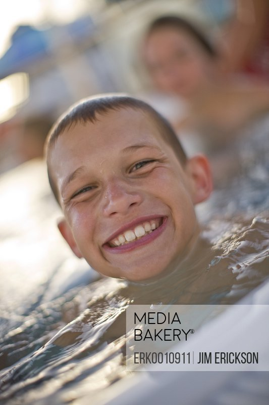 Portrait of a smiling young boy up to his neck in a swimming pool.